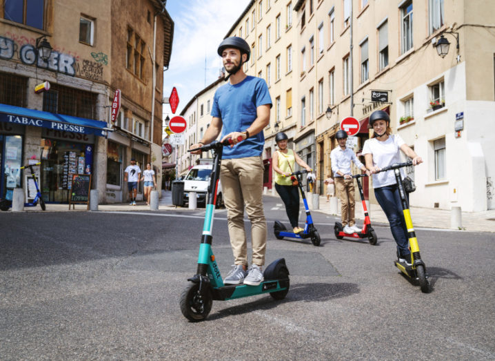 A group of people ride electric scooters through a European city.