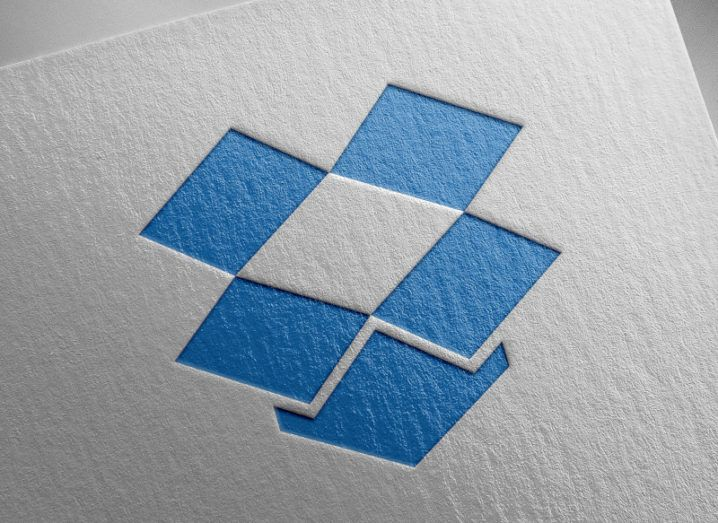 The Dropbox blue box logo on a piece of textured white paper.