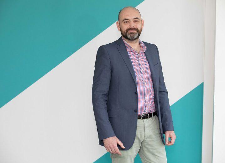 Empiric Logic CEO Gareth O'Sullivan stands against a bright wall.