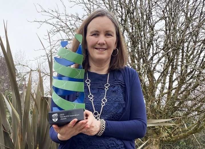 Fiona Doohan stands outdoors with her large blue and green NovaUCD award.