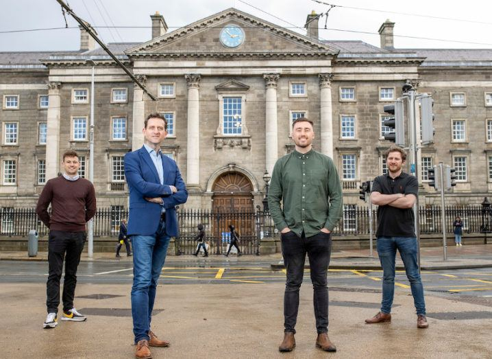 Four men stand a few metres apart in front of Trinity College Dublin.