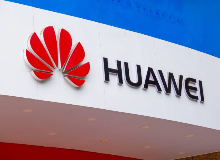 A Huawei logo on a white office building against a blue sky.