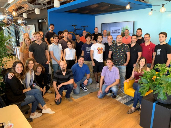 A large group of people pose together for a photo in a colourful office space.