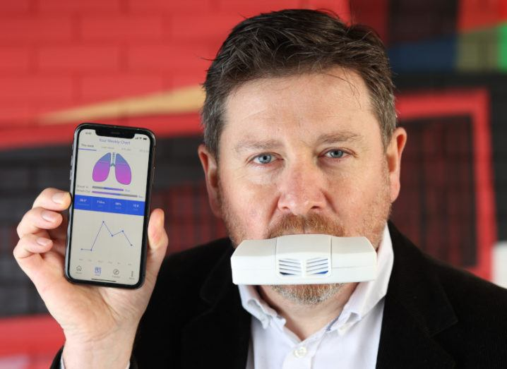 A man with an inhaler-like device in his mouth holds up his phone to display a graphic of lungs and collected health data from the device.