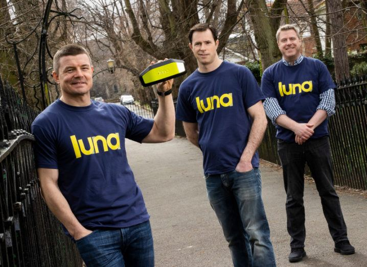 Brian O'Driscoll stands next to a park holding up a yellow computer vision device for e-scooters. Two men stand behind him, and all are wearing navy and yellow Luna T-shirts.