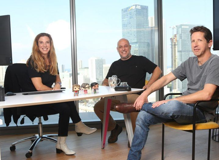 Executives of Incredibuild sitting at a table in an office room overlooking a city.