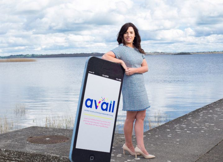 Avail Support founder Lisa Marie Clinton is standing on a beach wearing a blue dress and resting her arm on a giant prop smartphone with the company logo on it.