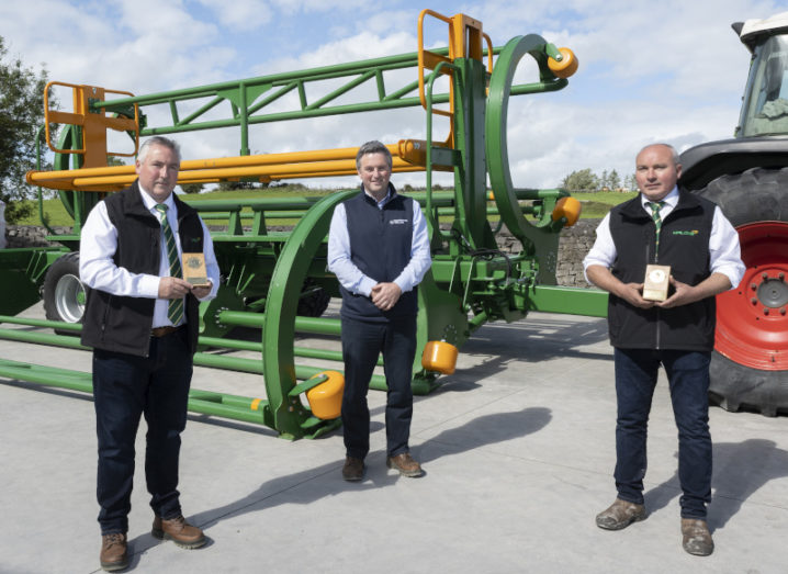 Three men stand in front of large farming machinery.