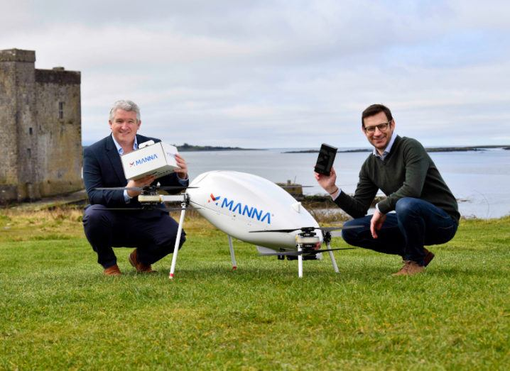 Two men crouch next to a drone. One is holding a Manna delivery box and the other is holding a Samsung S21 smartphone.