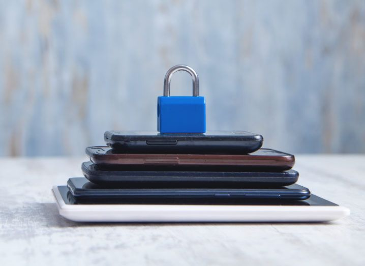 A small blue padlock sits on top of a pile of devices, symbolising data privacy.