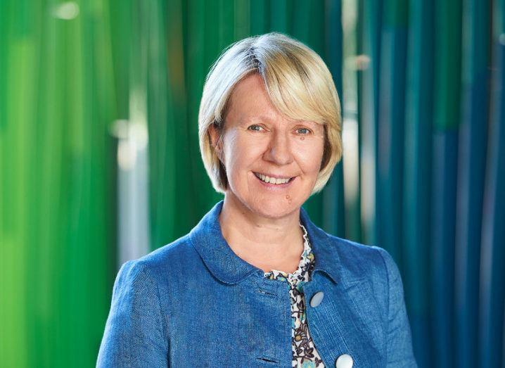Prof Eeva Leinonen is standing in a blue jacket against a green backdrop.