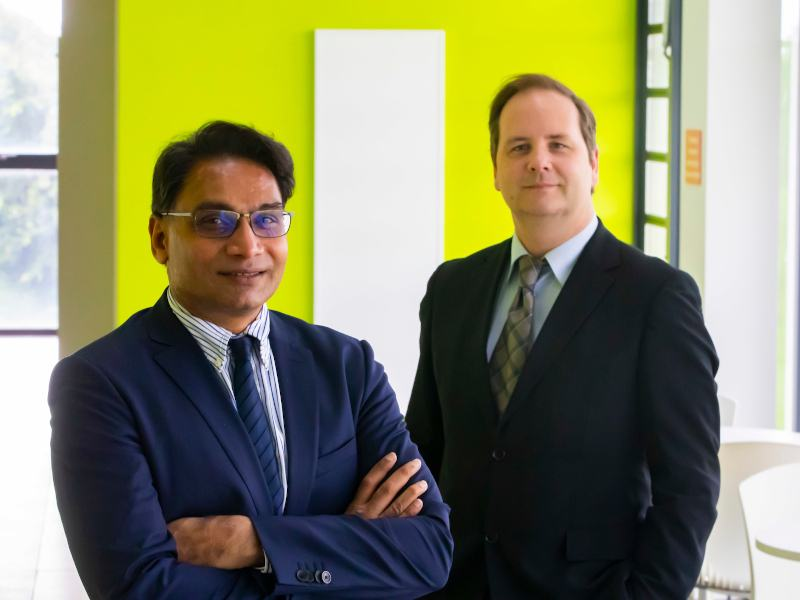 Two men in suits stand together in front of a neon green wall.