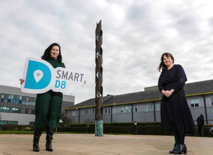 Two women stand in a large open courtyard with a large cylindrical structure in between them in the background. One is holding a sign that says Smart D8.