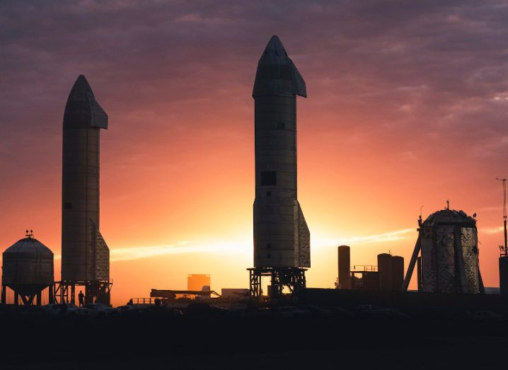 A close-up silhouette of a SpaceX Starship rocket ready for a flight test against a setting sun.