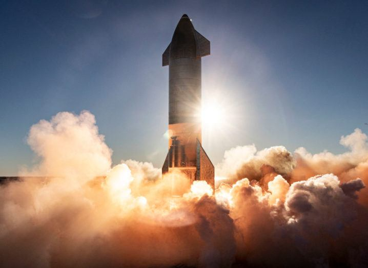 A SpaceX spacecraft takes off against a setting sun in a clear blue sky. The bottom of the rocket is engulfed in plumes of smoke.