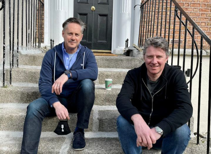 Two men sit in casual clothes on the steps of a Georgian building in Dublin. They are Strike founders Oli Cavanagh and Charles Dowd.