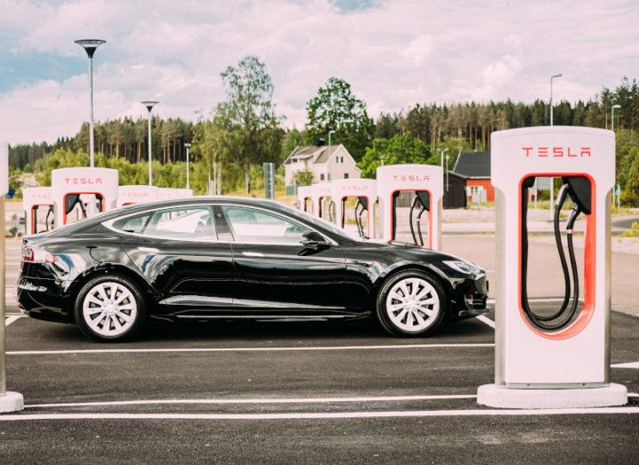 Black Tesla car in an empty car park on a sunny day. The car is surrounded by Tesla-branded charging stations.