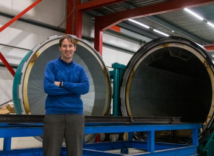 Tomás Flanagan, CEO of ÉireComposites, stands in a blue jumper in front of a large piece of manufacturing equipment.