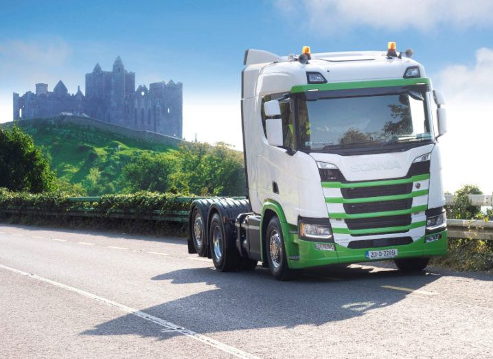 The front of a green and white truck parked on the side of a road with the Rock of Cashel in the background.