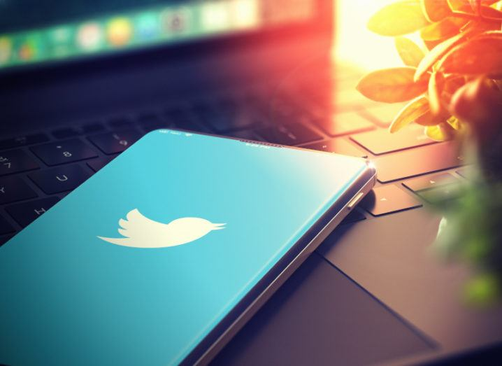 A smartphone sits on an open laptop. The phone has the Twitter logo on the screen and there's a sunset light shining on the laptop.