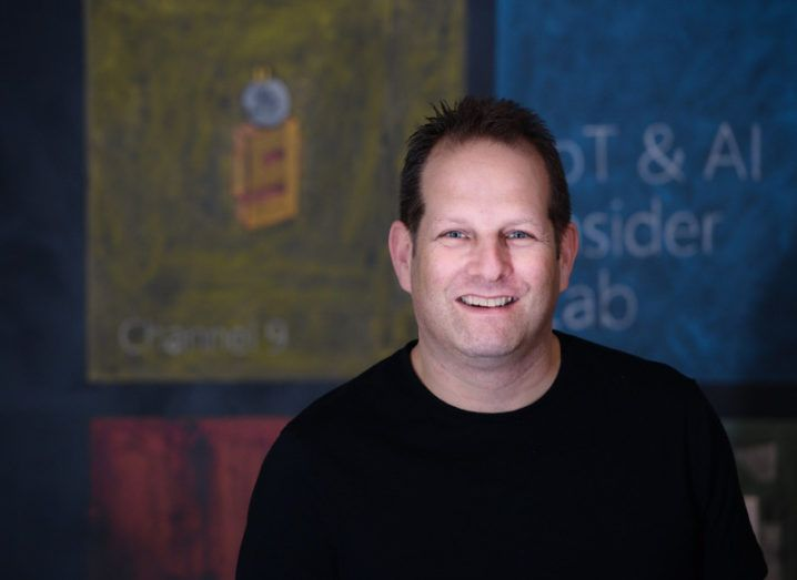 A man in a dark sweater stands in front of a wall bearing chalk illustrations.