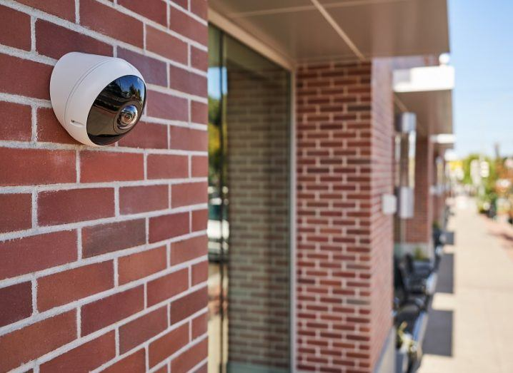 A surveillance camera made by Verkada placed on the wall outside a building.