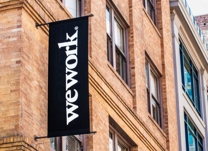 The side of a redbrick building with a black flag sign showing the WeWork logo.