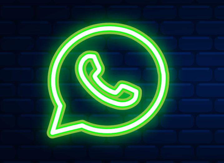 A neon green outline of the WhatsApp logo against a dark navy brick wall.
