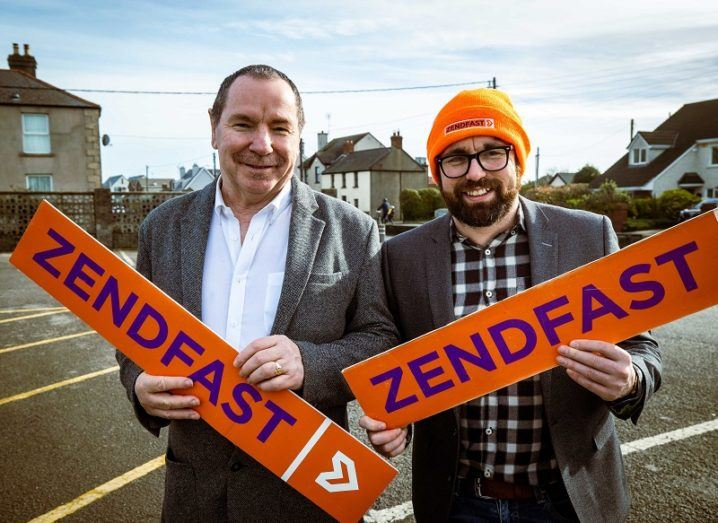 Declan and Colin Murray stand side by side in a car park holding orange signs that say Zendfast.