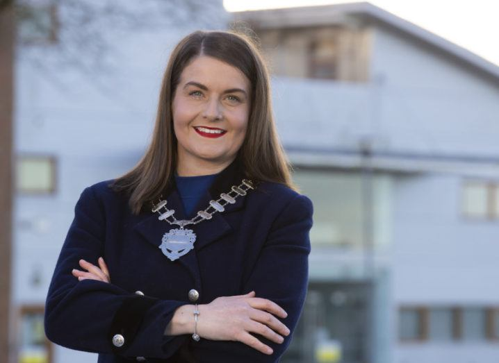 Aisling O'Neill stands outside ArcLabs wearing a suit and a gold chain.