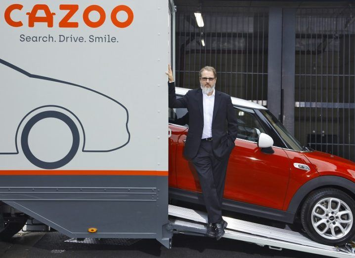 The founder of Cazoo standing in front of a car. The car is coming out of a van that has the Cazoo logo on the side.