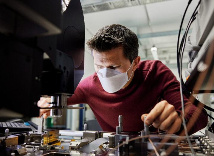 A masked engineer works on high-tech machinery at an Apple facility.