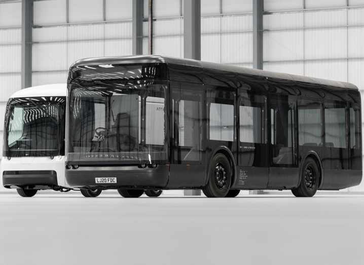 Black electric powered bus made by Arrival is sitting in a warehouse.