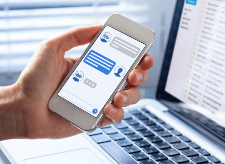 A person holding a phone with a chatbot on the screen, symbolising digital customer experience.