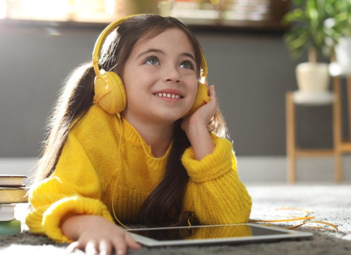 A little girl lies on a carpet wearing yellow headphones and listening to music on a tablet and smiling.