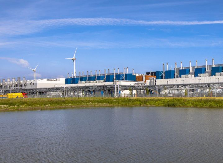 A large data centre facility in front of a body of water with wind turbines behind it.