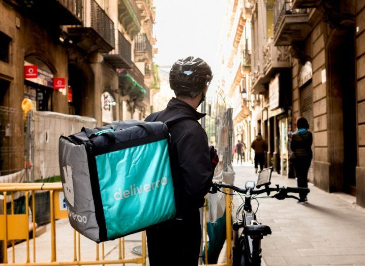 A person is standing on a street with a bicycle and a Deliveroo-branded backpack.