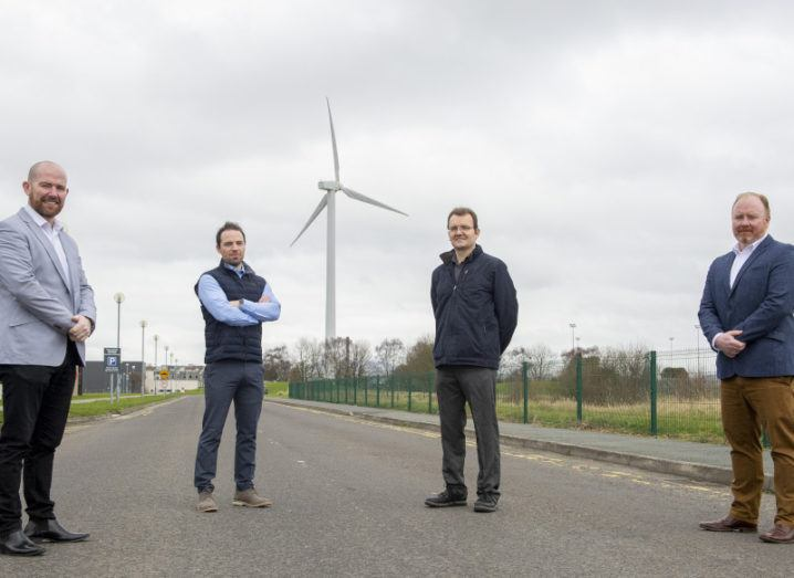Four men stand outside in front of a wind turbine.