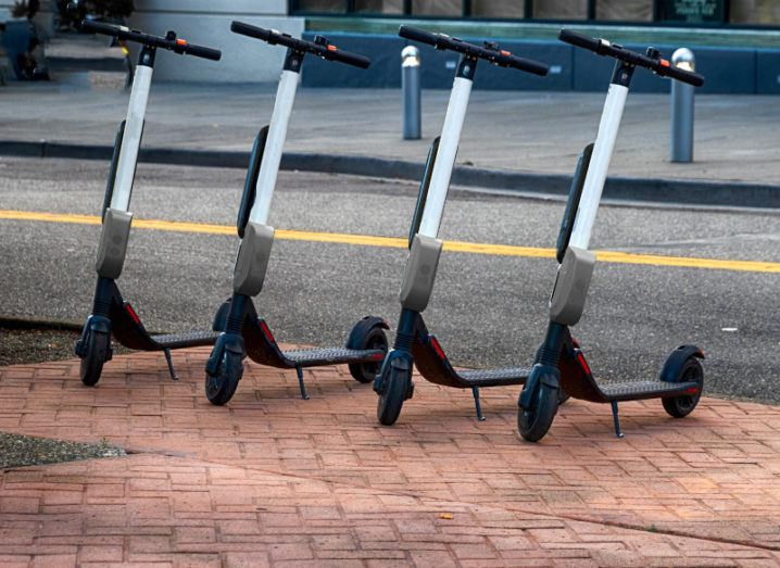 Four Bird e-scooters lined up and parked on a city street.
