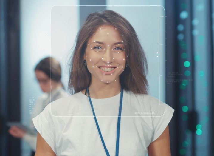 A facial recognition system detects a smiling woman's face.
