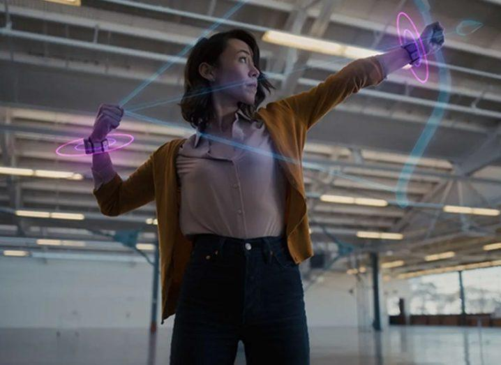 Woman using Facebook's neural wristband, in a pose that makes it look as though she is shooting an arrow.