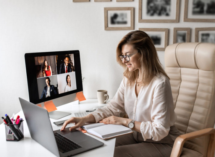 A woman works at a laptop in a home office, while a second screen is showing a video conference.