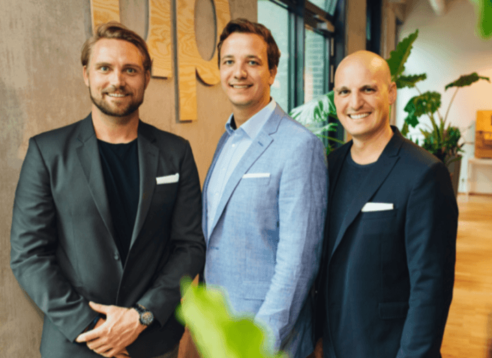 Three men from Productsup founding and leadership team are standing together in a bright office and smiling into the camera.