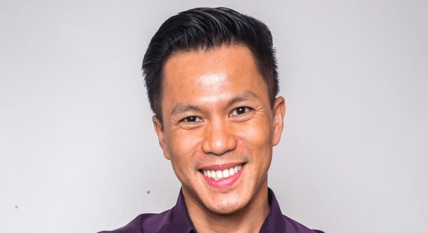 Jimmy Nguyen is smiling into the camera against a pale grey background.