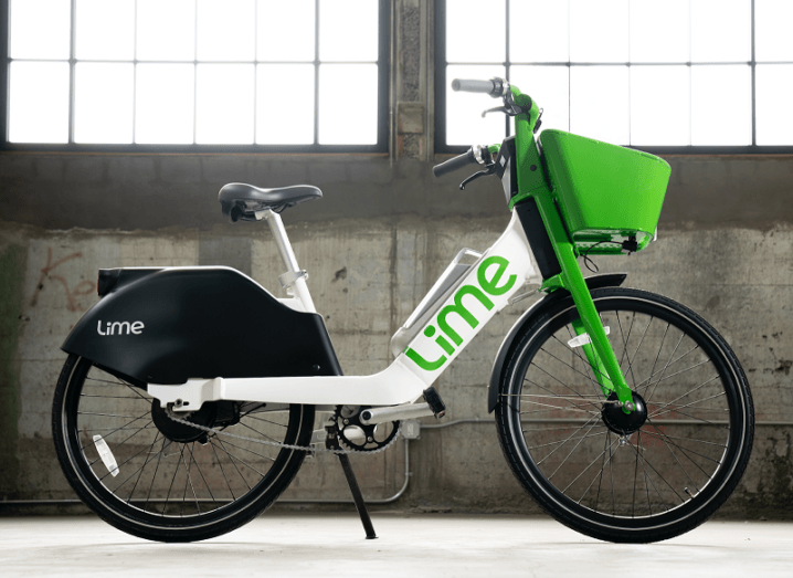 A white and green Lime-branded e-bike is standing in a warehouse.