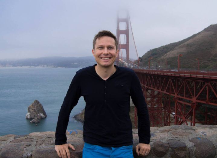 Dr Lukasz Porwol leans against a wall overlooking the Golden Gate Bridge in San Francisco on a misty day.