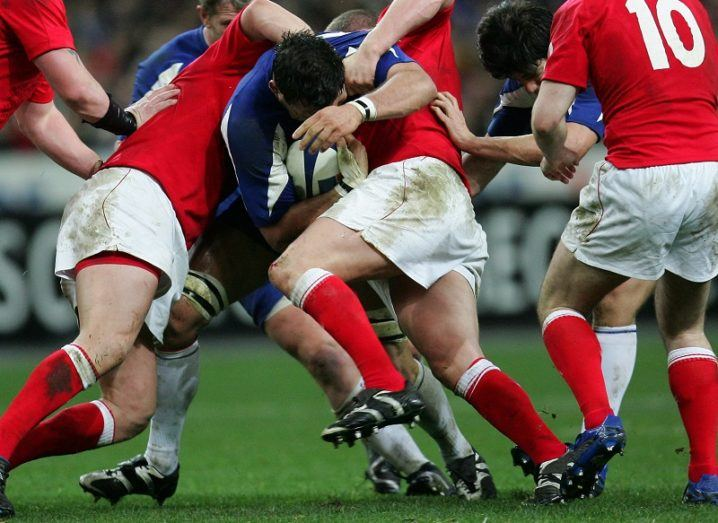 Rugby players tackling each for the ball on a sports pitch.
