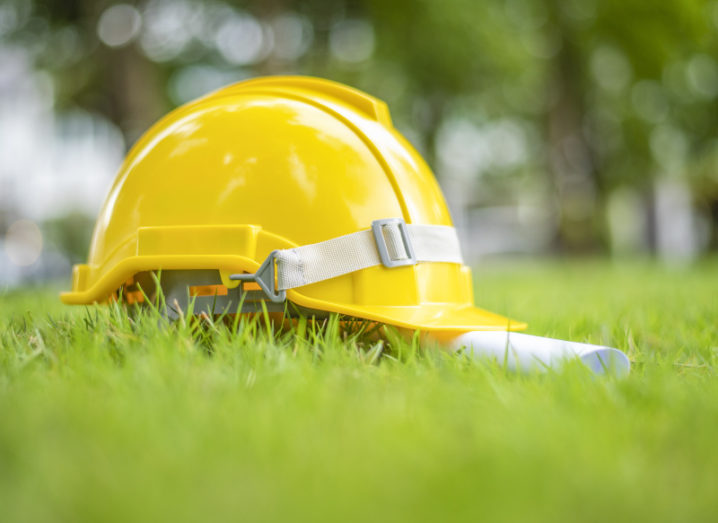 A yellow hard hat sits alongside a rolled up piece of paper on a patch of grass.