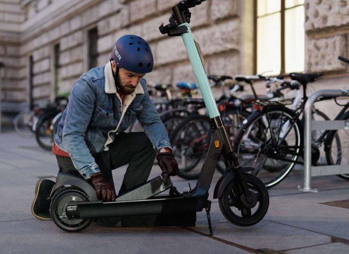 Man replacing the battery in a Tier electric scooter.