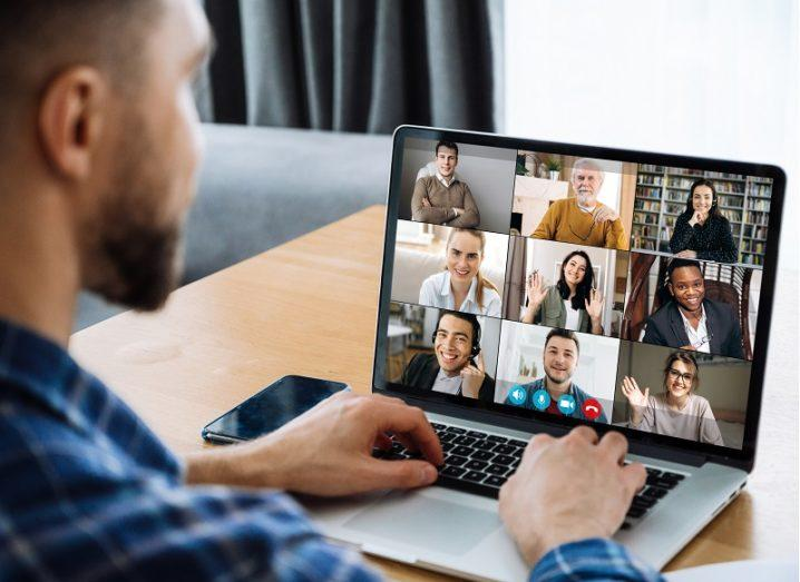 Man sitting in on a virtual meeting with colleagues on his laptop.